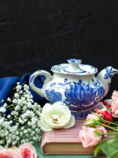 front-close-up-view-white-blue-kettle-around-blue-tissue-different-colored-roses-dark-floor_140725-14252
